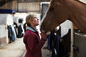 Stable hand talking to horse in stables