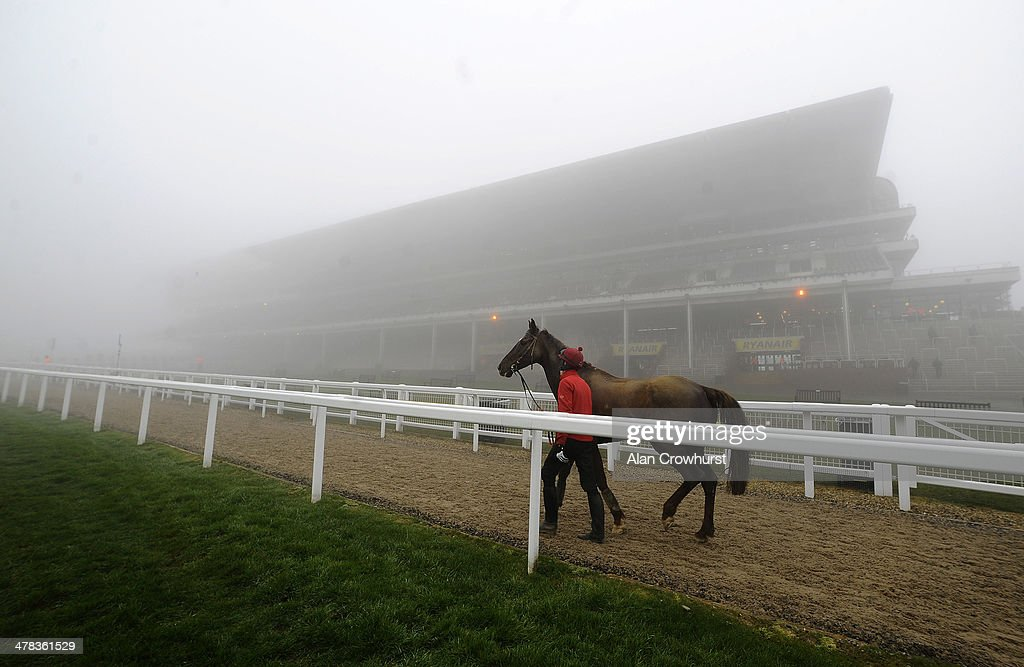 A stable lad returns to the stables on a foggy morning on St Patrick's Thursday during the Cheltenham Festival at Cheltenham racecourse on March 13, 2014 in Cheltenham, England.