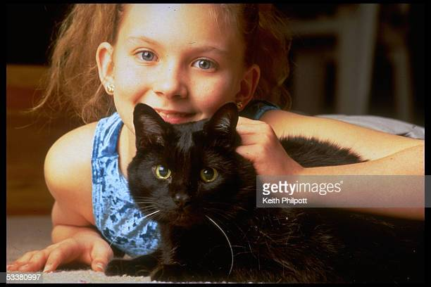 Stacey Rogers with her cat Midnight who saved her from crib death when she was an infant alerting her mother Bernita by meowing through a baby...