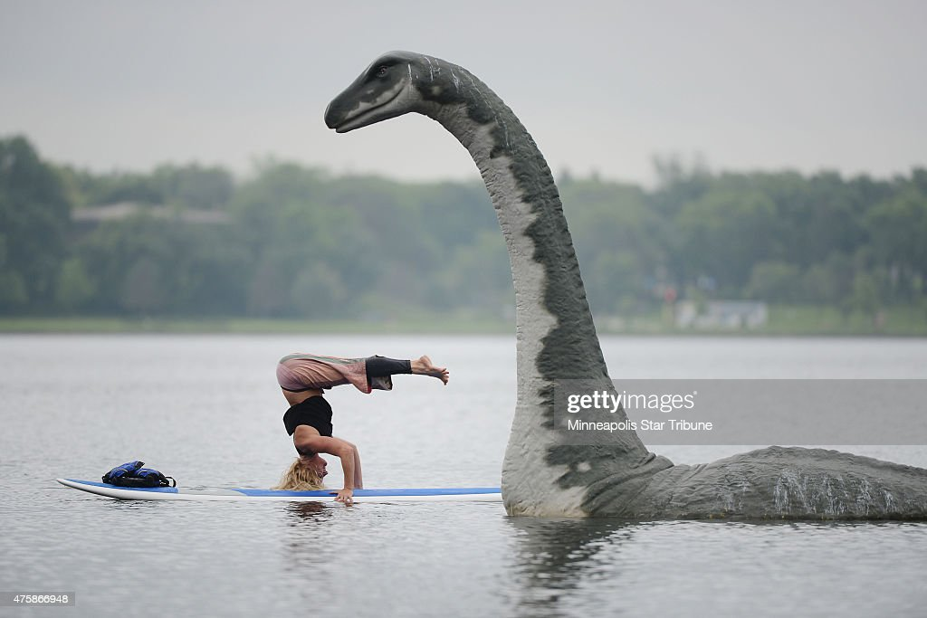 Stachia Fey of the Wai Nani Surf and Paddle Tribe strikes a yoga pose on her paddle board next to Minne the 13foot fiberglass lake creature on Lake...