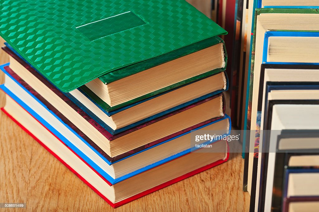 Stack and a number of books on a wooden surface. : Stock Photo