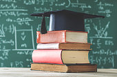 Stack books  graduate hat in front of  green chalkboard