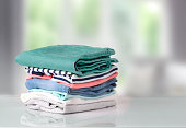 Stack of clothes on table indoor.Household concept.Fresh folded cotton clothing.