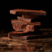 Chocolate bars stack isolated on a dark marble background