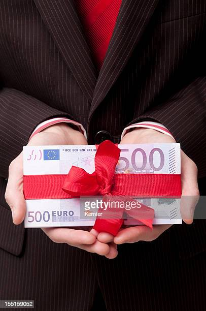 A stack of 500 euro banknotes tied with a red ribbon
