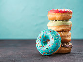 Stack of assorted donuts on black and blue cement background. Blue glazed doughnut with sprinkles on foreground. Copy space. Shallow DOF