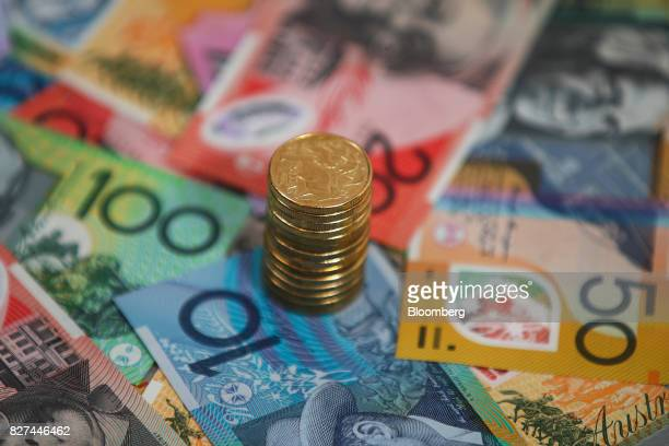 A stack of Australian one dollar coins and banknotes of various denominations are arranged for a photograph in Sydney Australia on Friday Aug 4 2017...
