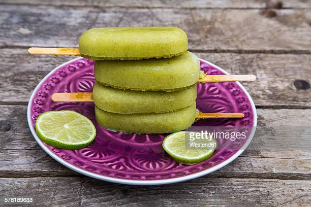 Stack of avocado ice lollies and slices of lime on plate