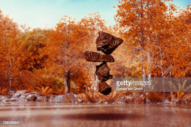 Stack of balancing rocks hovering mid-air in autumn