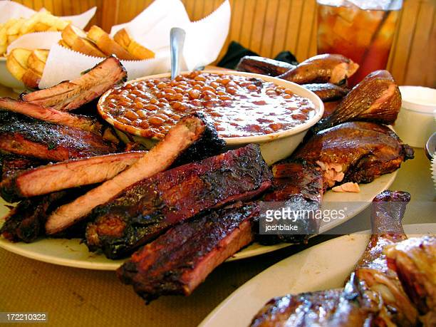 A stack of BBQ ribs served with dipping sauce