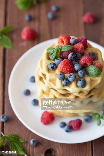 A stack of Belgian waffles with raspberries and blueberries