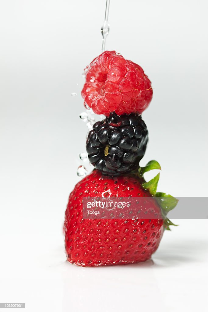 Stack of berries with water pouring on top  : Stock Photo
