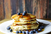 A stack of homemade blueberry pancakes with fresh blueberries and Maine maple syrup