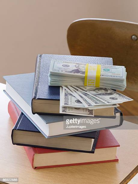 Stack of books and money on school desk