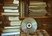 stack of books, library, cd, headphones, wooden table and bookcase