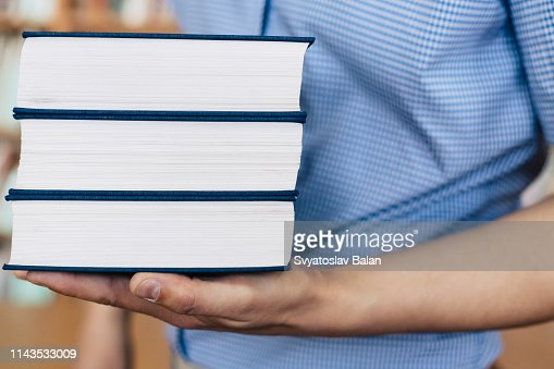 Stack of books lying on the palm : Stock Photo