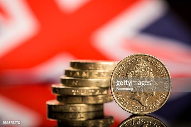 A stack of British one pound sterling coins stand in front of a British Union flag also known as a Union Jack in this arranged photograph in...