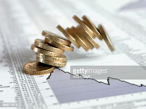 Stack of British pound coins falling on list of share prices : Stock Photo