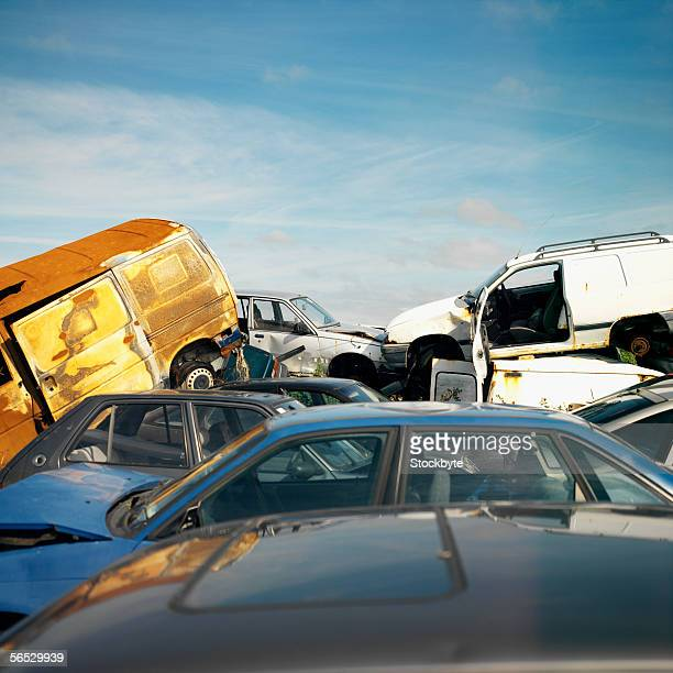 stack of broken cars in a junkyard