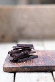 Stack of broken dark chocolate bar pieces on a wooden background