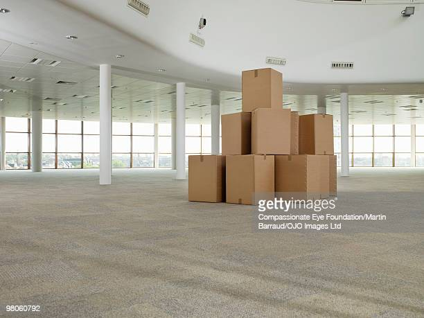 stack of cardboard boxes in middle of empty room