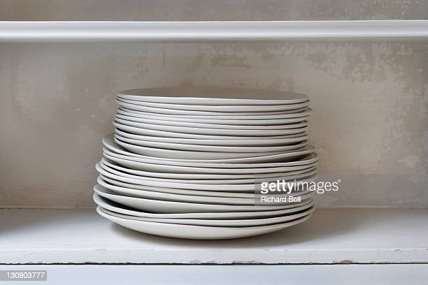 A stack of ceramic dining plates on a shelf.