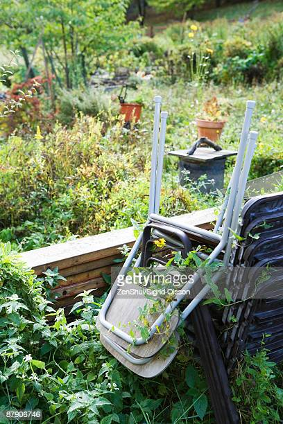 Stack of chairs in overgrown garden