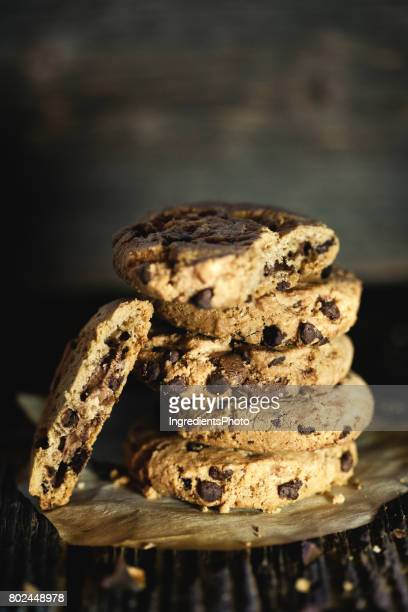 Stack of chocolate chip cookies on a wooden table.