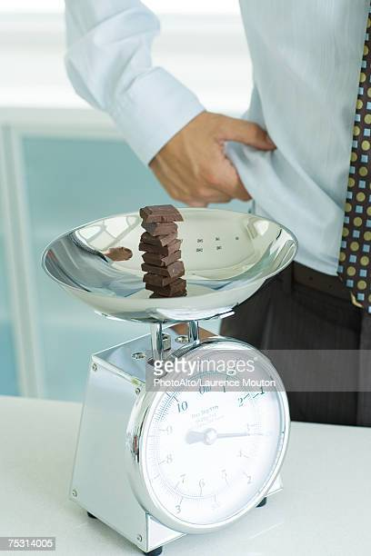 Stack of chocolate chunks on kitchen scale, and man pinching waist