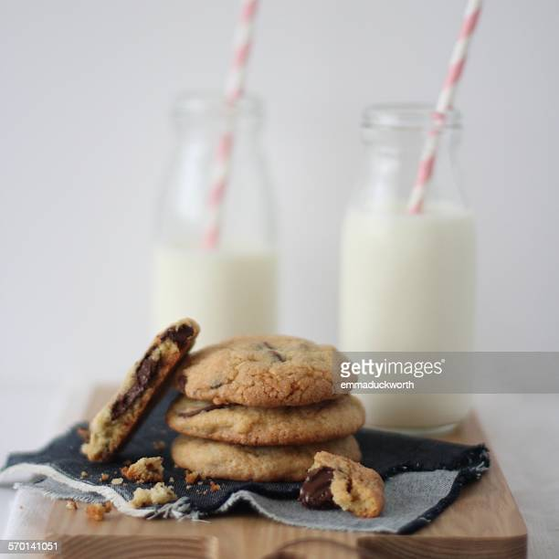 Stack of chocolate cookies with bottles of milk