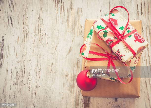 Stack of Christmas presents and red Christmas bauble on wood