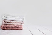 Stack of clean towels on wooden table in bathroom