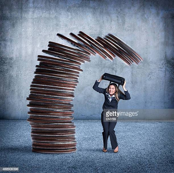 Stack Of Coins About To Fall On Businesswoman