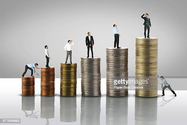 Stack of coins from low to high,tiny men on top