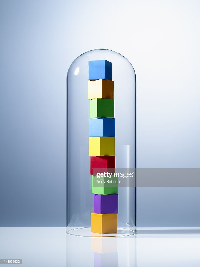 Stack of colorful cubes under glass jar