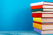 Stack of colorful hardback books, open book on blue background