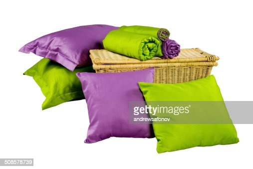 stack of colorful pillows and twisted blankets on baskets : Stock Photo