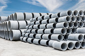 Stack of concrete drainage pipes for wells and water discharges with blue sky