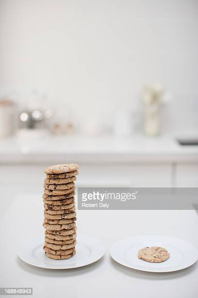 Stack of cookies on plate next to single cookie on plate