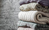Stack of cozy knitted sweaters on gray wall background