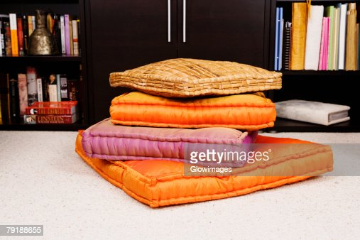 Stack of cushions in front of a cabinet : Foto de stock