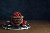 A tall stack of dark chocolate pancakes topped with fresh raspberries and red currants on a metal dish. The pancakes are on a wooden table top in front a dark blue wall. There is copy space for text i