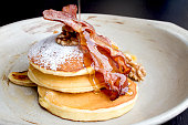 Stack of delicious pancakes with bacon, honey, nuts and caramelize banana