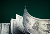 stack of hundred dollars notes on dark green background