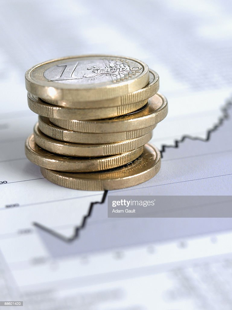 Stack of euro coins on ascending line graph : Stock Photo