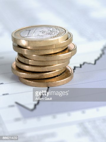 Stack of euro coins on ascending line graph : Photo