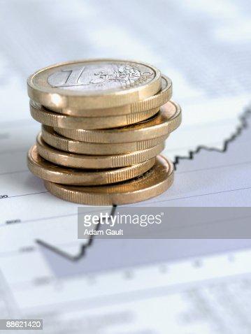 Stack of euro coins on ascending line graph : Bildbanksbilder