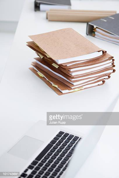 Stack of files, laptop and folders in conference room