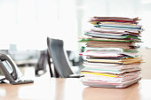 Stack of files on tray next to telephone at office desk