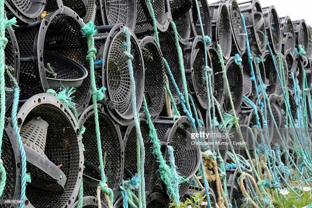Stack Of Fishing Cages With Ropes On Grass